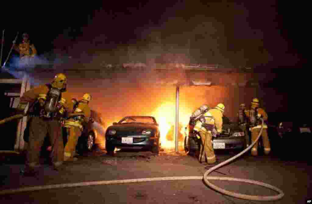 L.A. Fire Department firefighters extinguish cars in a carport in the Sherman Oaks neighborhood of Los Angeles on Monday, January 2, 2012. (AP)
