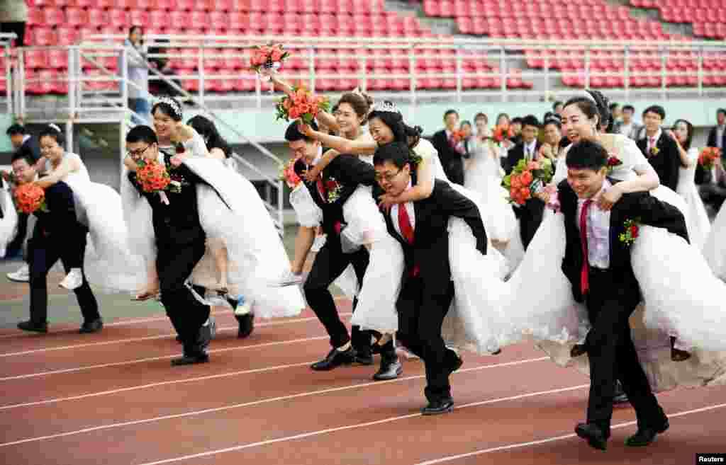 """黑龙江哈尔滨工业大学64对博士生的集体婚礼上举行背媳妇赛跑(2017年6月4日)。新娘们穿着婚纱。中国婚纱礼服网的一篇文章说:""""国人真正开始接触白色婚纱还要追溯到20世纪80年代,在此之前一直秉承红色凤冠霞帔的传统将近3000年之久。面对改革开放带来的外来文化的强烈冲击,婚纱变成了婚礼服饰的代名词。""""其实,在西风东渐的民国时代,也有不少新娘穿西方式婚纱。也有新娘穿中西合璧的婚纱,例如本图集最后一图上的宋美龄结婚照。"""