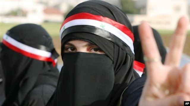 A Syrian protester flashes the victory sign during a protest calling for President Bashar Assad to step down in front of the Syrian embassy in Amman, Jordan, Sunday, April 17, 2011.