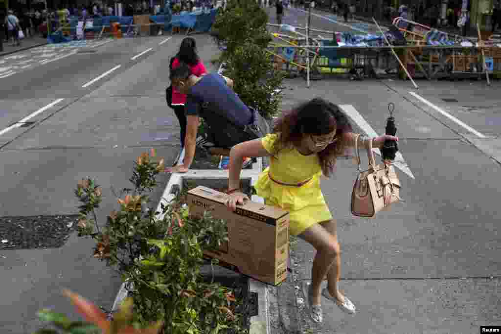 A mainland Chinese visitor jumps over a planter as she crosses a road blocked by the Occupy Central movement protesters on the Mong Kok shopping district in Hong Kong, Oct. 6, 2014.