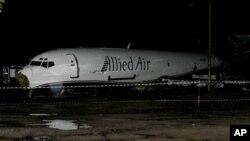 Badan pesawat kargo Boeing 727 teronggok menutupi jalanan di dekat Bandara Internasional Kotoka di Accra, Ghana (2/6). Pesawat kargo tersebut gagal mendarat di bandara dan menabrak sebuah bus sarat penumpang di jalan di dekatnya. 10 orang dilaporkan tewas