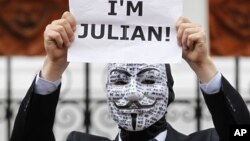 A supporter of WikiLeaks founder Julian Assange holds up a placard outside the Ecuadorian Embassy in central London, London, August 16, 2012.