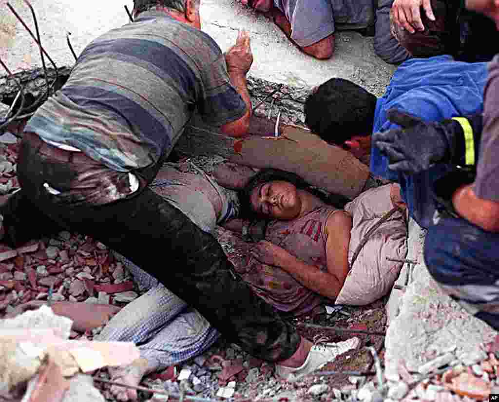A woman lies trapped in rubble next to a companion as rescue workers try to dig her out of her collapsed home in Istanbul, August 17, 1999. (Reuters)