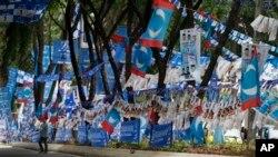 Seorang warga Malaysia berjalan melewati poster dan bendera kampanye dari kedua partai yang saling bersaing dalam pemilu Minggu mendatang - partai Barisan Nasional yang berkuasa dan partai oposisi Keadilan Rakyat - yang menghiasi sisi sebuah jalan di Malaysia menjelang pemilu (1/5).
