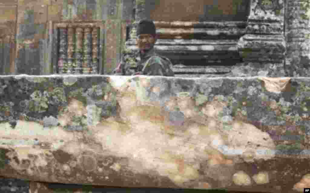 A Cambodian army soldier sits at damaged Cambodia's 11th century Hindu Preah Vihear temple.