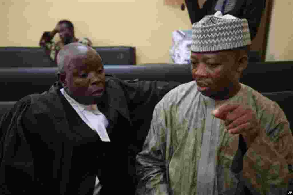 Nigerian Usman Abbas Jega, right, charged with Iranian Azim Aghajani, for orchestrating an illegal arms shipment in to Nigeria that contained mortars and military-grade weapons, discusses with his lawyer before his trial, at the Federal High Court in Lago