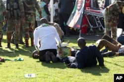 FILE - Injured people are attended to as they lay on the ground following an explosion at a Zanu pf rally in Bulawayo, June, 23, 2018.