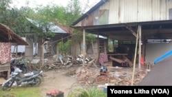 Seorang warga di depan rumah yang kehilangan bagian dinding yang roboh dalam gempa bumi magnitudo 6,2 di Majene, Sulawesi Barat. Jumat, 29 Januari 2021. (Foto: VOA/Yoanes Litha)