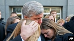 Former Virginia Gov. Bob McDonnell (C) hugs two of his daughters Cailin Young (L), and Jeanine McDonnell Zubowsky (R) after speaking outside federal court in Richmond, Va., Jan. 6, 2015.
