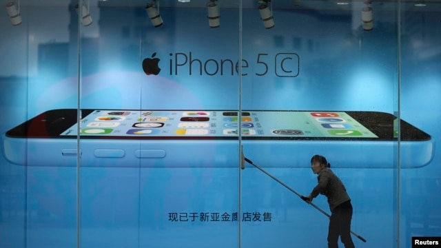 Worker cleans glass in front of an iPhone 5C advertisement at an apple store in Kunming, Yunnan province, China, Oct. 27, 2013.