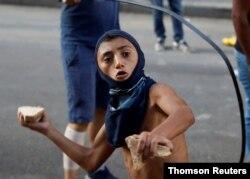 10일 레바논 베이루트에서 벌어진 반정부 시위에서 참가자가 경찰을 향해 돌을 던지고 있다.