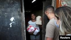 Daniele de Fatima, stands at her house in Cidade de Deus slum, as she receives food and bread from members of the Institute doAcao, which was produced at the Santuario de Nossa Senhora de Fatima, amid COVID-19 outbreak, in Rio de Janeiro, June 24, 2021.