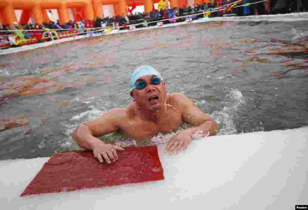 A swimmer reacts after finishing his competition in a pool carved into thick ice covering the Songhua River during the Harbin Ice Swimming Competition in the northern city of Harbin, Heilongjiang province, China.