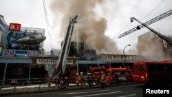 Pemadam kebakaran berusaha mengatasi kobaran api di pasar ikan Tsukiji di Tokyo, Jepang hari Kamis (3/8).