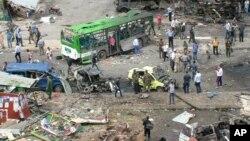 Pasukan keamanan Suriah memeriksa lokasi ledakan bom di sebuah stasiun bis di kota pesisir Tartus hari Senin (23/5).
