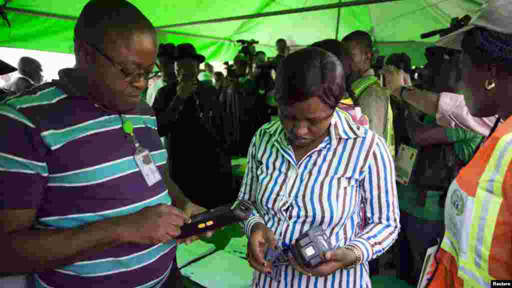 Officials of the Independent National Electoral Commission troubleshoot card readers after they failed to capture President Goodluck Jonathan's card at his polling unit in Otuoke, Bayelsa State, March 28, 2015.
