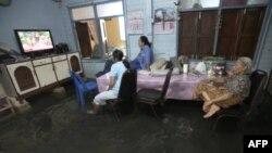 Một gia đình ngồi xem TV trong căn nhà bị ngập ở Bangkok, Thái Lan, ngày 3/10/2011
