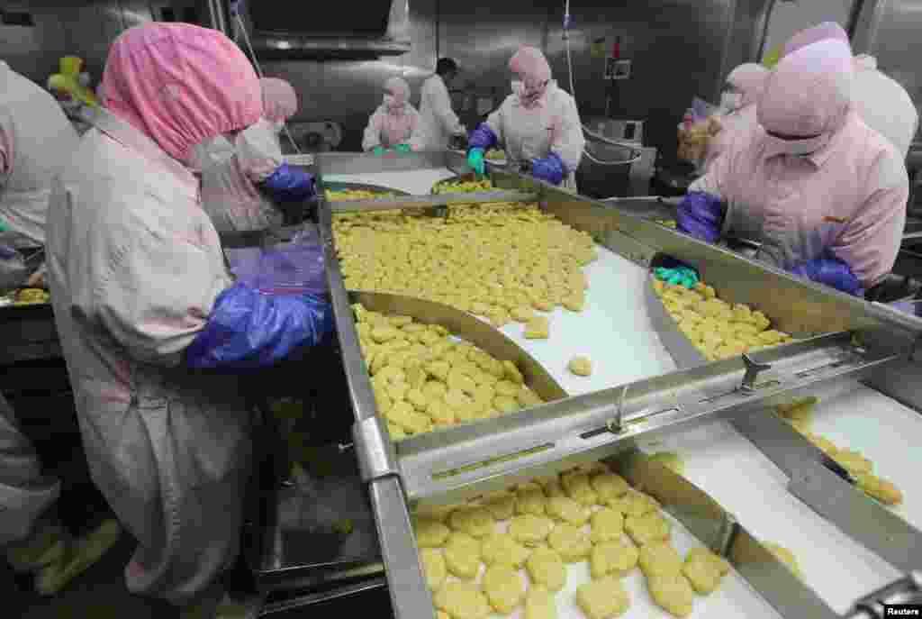 Nhân viên làm việc tại một dây chuyền sản xuất tại nhà máy thực phẩm Husi ở Thượng Hải, Trung Quốc, ngày 20 tháng 7, 2014. Cục Thực phẩm và Dược phẩm Thượng Hải đóng cửa nhà máy thực phẩm Husi và tịch thu các sản phẩm thịt bị nghi ngờ là quá hạn sử dụng.