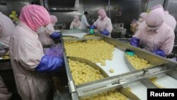 Employees work at the Husi Food factory prior to a seizure from the Shanghai Food and Drug Administration July 20, 2014.