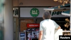 "A man stands nearby as a ""24/7"" open sign is seen at the entrance of a food store in Tel Aviv, Israel, Sept. 20, 2016."