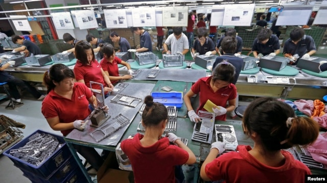 FILE - Employees work at a Foxconn factory in Wuhan, Hubei province, China.