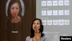 A woman is reflected in Panasonic Corp's interactive mirror, which is able to apply virtual makeup and detect skin condition, during a demonstration at CEATEC (Combined Exhibition of Advanced Technologies) JAPAN 2015 in Makuhari, Japan, October 6, 2015.