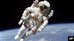 This Feb. 7, 1984 photo made available by NASA shows astronaut Bruce McCandless II, participating in a spacewalk a few meters away from the cabin of the Earth-orbiting space shuttle Challenger, using a nitrogen-propelled Manned Maneuvering Unit.