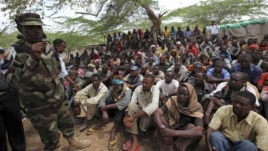 Members of al- Qaida-linked militant group al-Shabab listen to a Somalia government soldier after their surrender to the authorities in the north of Somalia's capital Mogadishu, September 24, 2012.