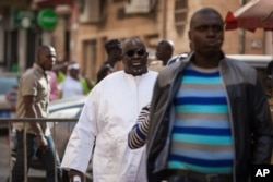 FILE - Papa Massata Diack, center, son of former IAAF President Lamine Diack, arrives at the central police station in Dakar, Senegal, Feb. 17, 2016.