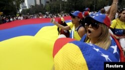 FILE - People carry a giant Venezuelan flag during a protest of Venezuelan citizens residing in Mexico, against the government of Venezuela's President Nicolas Maduro and the violence resulting from anti-government protests, in Mexico City, Feb. 23, 2014.