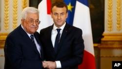 El presidente francés, Emmanuel Macron (derecha) saluda a su homólogo palestino, Mahmoud Abbas, durante una conferencia de prensa conjunta en París, el viernes 22 de diciembre.