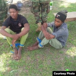 Young men described as foreign fighters are seen after being captured by the Nigerian military during an operation in Balmo forest. (Nigerian Ministry of Defense)