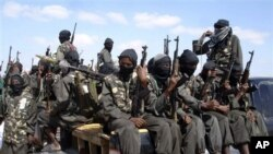 FILE - Armed fighters from the al-Shabab group travel on the back of pickup trucks outside Mogadishu in Somalia, Dec. 8, 2008.
