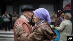 In this 2014 photo, a Ukraine couple attend a public dance. Activities like this may help to keep the brain young -- hers perhaps a little longer than his. (AP Photo/Alexander Zemlianichenko)