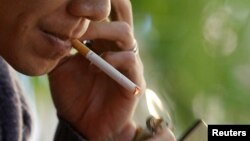 A man lights a cigarette at a cafe in Hanoi, Vietnam, November 12, 2012.