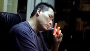 In this June 30, 2010 file photo, Prominent Chinese human rights lawyer Pu Zhiquiang lights a cigarette during an interview at his office in Beijing.