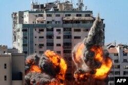 Bola api meletus dari Menara Jala saat hancur dalam serangan udara Israel di Kota Gaza, yang dikendalikan oleh gerakan Hamas Palestina, pada 15 Mei 2021. (Foto: AFP)