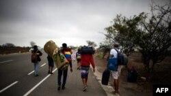 Migrantes venezolanos caminan a lo largo de una ruta, en Tumbes, Perú, cerca de la frontera con Ecuador.