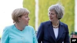 La Chancelière Angela Merkel, à gauche, la Premier ministre Theresa May marchent vers une cérémonie militaire à Berlin, le 20 juillet 2016.