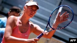 FILE - Russian tennis player Maria Sharapova touches her racket at the end of her match against Colombian Mariana Duque Marino in Madrid on May 5, 2015. Sharapova's racket supplier says it is planning to extend its sponsorship deal despite the five-time Grand Slam champion admitting to failing a doping test.