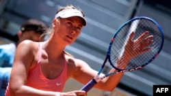 FILE - Russian tennis player Maria Sharapova touches her racket at the end of her match against Colombian Mariana Duque Marino in Madrid, Spain, on May 5, 2015.