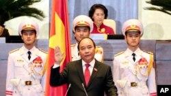 Nguyen Xuan Phuc, center, takes oath after being elected as prime minister in Hanoi, Vietnam Thursday April, 7, 2016. (Thong Nhat/Vietnam News Agency via AP)