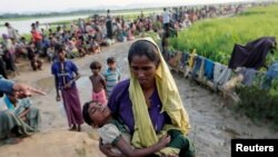 Seorang wanita pengungsi Rohingya yang melintasi perbatasan dari Myanmar sehari sebelumnya, menunggu untuk mendapat izin dari tentara Bangladesh untuk melanjutkan perjalanan ke kamp-kamp pengungsian, di Palang Khali, Bangladesh, 17 Oktober 2017.
