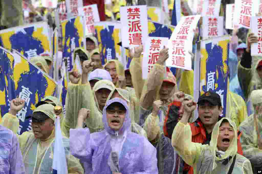 "Labor rights activists shout while holding signs reading ""Forbid Temporary Worker Services"" during a rally for labor rights on international Labor Day in Taipei, Taiwan."