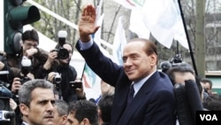 Perdana Menteri Italia, Silvio Berlusconi melambai saat meninggalkan kantor pengadilan di Milan.