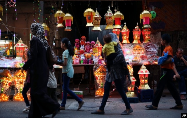 Palestinians walk in front of traditional lighted Ramadan lanterns, marking the holy month of Ramadan at main market in Gaza City, June 3, 2016.