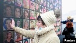 Kerabat korban menghadiri upacara peringatan setahun jatuhnya pesawat milik maskapai Ukraina International Airlines PS752 yang jatuh di wilayah udara Iran, di Kyiv, Ukraina, 8 Januari 2021. (REUTERS / Valentyn Ogirenko)