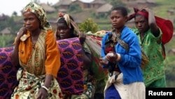 FILE - Women carry their belongings as they return to Kanyabayonga town, Democratic Republic of Congo.