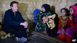British Prime Minister David Cameron meets Syrian refugee families at a tented settlement camp in the Bekaa Valley on the Syrian - Lebanese border, Sept. 14, 2015.