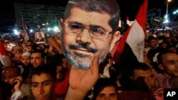 Mohamed Morsi has been ousted as president of Egypt, and his supporters, one holding a Morsi mask, are demanding his reinstatement.
